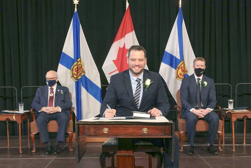 Derek Mombourquette signs his oath of office after being sworn in as Nova Scotia's minister of education on Feb. 23, 2021. -- Communications Nova Scotia