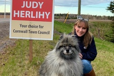 Judy Herlihy poses near one of her campaign signs in Cornwall with her dog. She won the town's recent byelection with 232 votes.