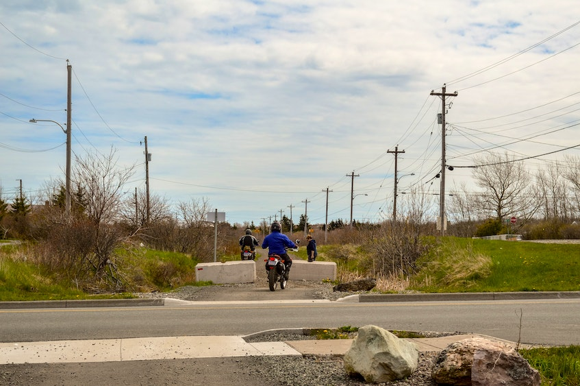 A resident walking her dogs moves aside on the Coal Town Trail for a couple of passing dirt bikers in Dominion. JESSICA SMITH • CAPE BRETON POST