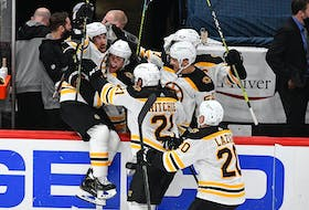 Boston Bruins centre Brad Marchand (left) jumps into his teammates' arms after scoring the winning goal in overtime against the Washington Capitals at Capital One Arena on Monday. - Brad Mills-USA TODAY Sports
