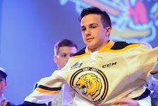 Charlottetown Islanders winger Cedric Desruisseaux pulls on the Victoriaville Tigres jersey after being drafted by them in the first round of the 2016 Quebec Major Junior Hockey League draft at the Eastlink Centre.