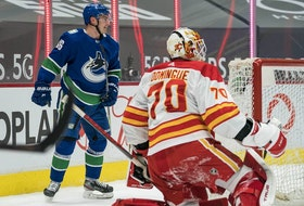 Canucks forward Nils Hoglander scores on Calgary Flames goalie Loius Dominque as defenceman Nikita Nesterov looks on  in the first period at Rogers Arena in Vancouver. Mandatory Credit: Bob Frid-USA TODAY Sports ORG XMIT: IMAGN-445772