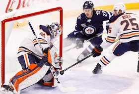 Winnipeg Jets center Mason Appleton (22) and Edmonton Oilers defenceman Darnell Nurse (25) watch as Edmonton Oilers goaltender Mike Smith (41) blocks a shot at Bell MTS Place on April 17, 2021.