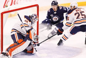 Winnipeg Jets center Mason Appleton (22) and Edmonton Oilers defenceman Darnell Nurse (25) watch as Edmonton Oilers goaltender Mike Smith (41) blocks a shot at Bell MTS Place on April 17, 2021.