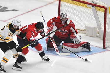 Washington Capitals right wing T.J. Oshie (77) clears the puck from Boston Bruins center Sean Kuraly (52) as goaltender Craig Anderson (31) looks on during the first period in game two of the first round of the 2021 Stanley Cup Playoffs at Capital One Arena.
