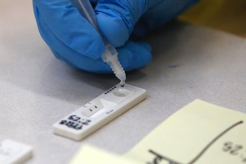 A sample from a patient's swab test, drops on a test strip at a rapid testing site at Central Spryfield School in Halifax Tuesday May 18, 2021.