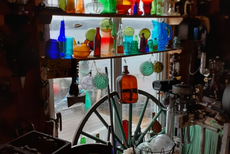 Glass items, including bottles and lamps, surround one of the shed's windows. — Paul Herridge