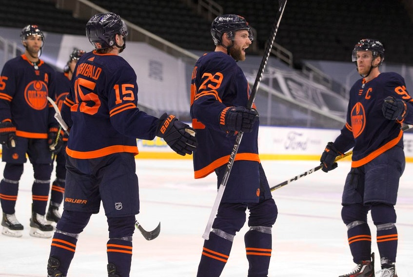 Edmonton Oilers Josh Archibald (15) celebrates his empty net goal with teammates Leon Draisaitl (29) and Connor McDavid (97) against the Calgary Flames during third period NHL action on Saturday, May 1, 2021 in Edmonton.
