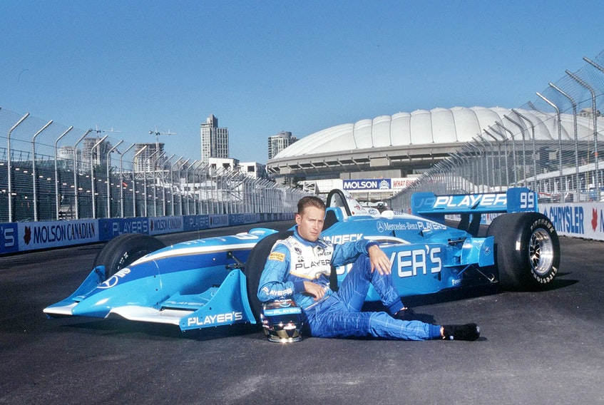 Hometown hero Greg Moore strikes a pose with his Indy car on the home straight at Vancouver's then-new Indy track in 1998.  Chris Relke photo