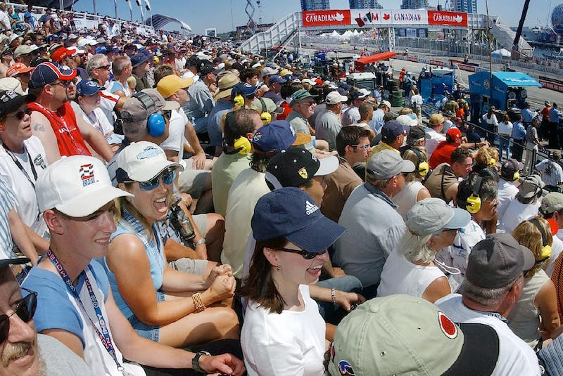 Dana Andjelkovic (yelling at cars, white cap) and thousands of others soaked up the hot sun on race day back in the day. Mark van Manen photo - POSTMEDIA