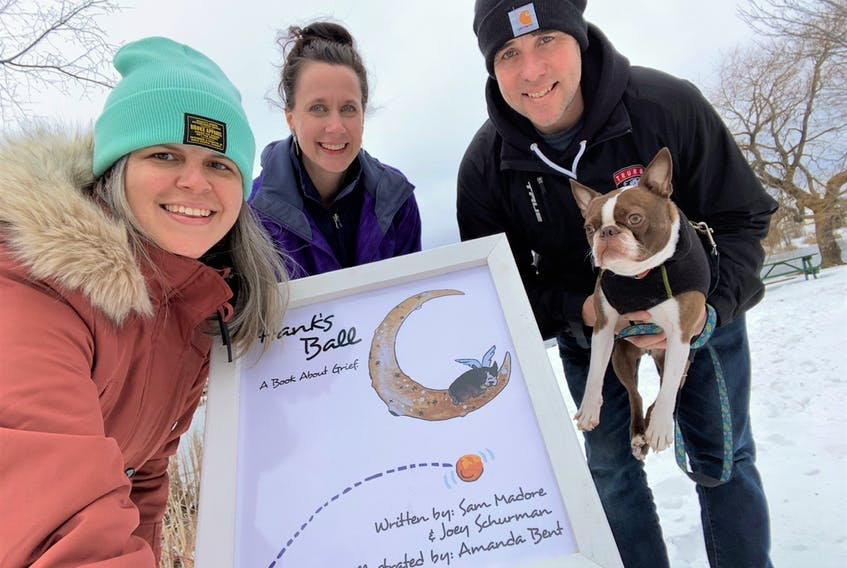 Sam Madore (left), Amanda Bent and Joey Schurman with Bert, gather around the blown-up cover to Hank's Ball, their book used for Story Trail which was set-up around Kiwanis Pond from February to earlier this month. The trio has recently completed a new book – Bert's Tool Box.