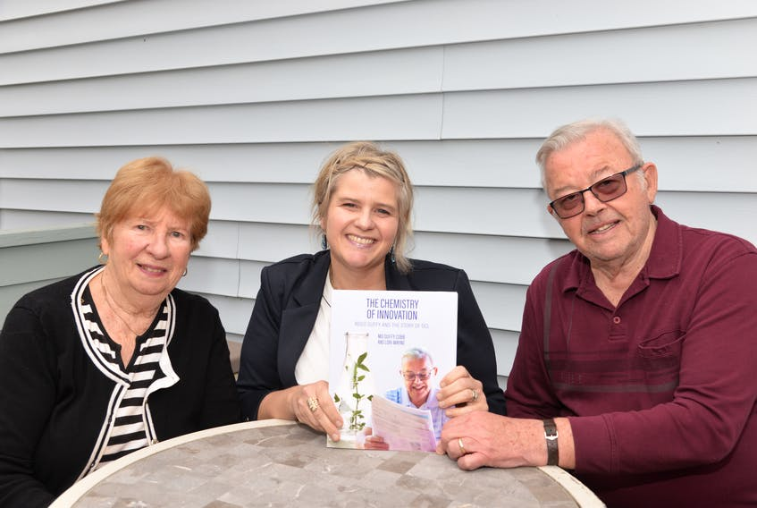 Regis Duffy, right, holds a copy of The Chemistry of Innovation: Regis Duffy and the story of DCL (Diagnostic Chemicals Limited) with his wife Joan Duffy, left, and daughter Mo Duffy Cobb. The book was co-written by Cobb and Lori Mayne.