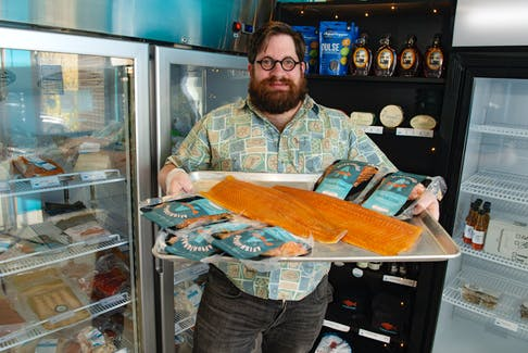 Chad Poirier holds a tray with smoked salmon from Afishionado in Bedford on Tuesday, May 25, 2021.
