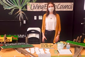 """Jessica Frenette and other volunteers handed out signs made of upcycled wood, posters and seeds at the Truro Farmers' Market for people to proudly display and promote the """"No Mow May"""" concept on their lawns."""
