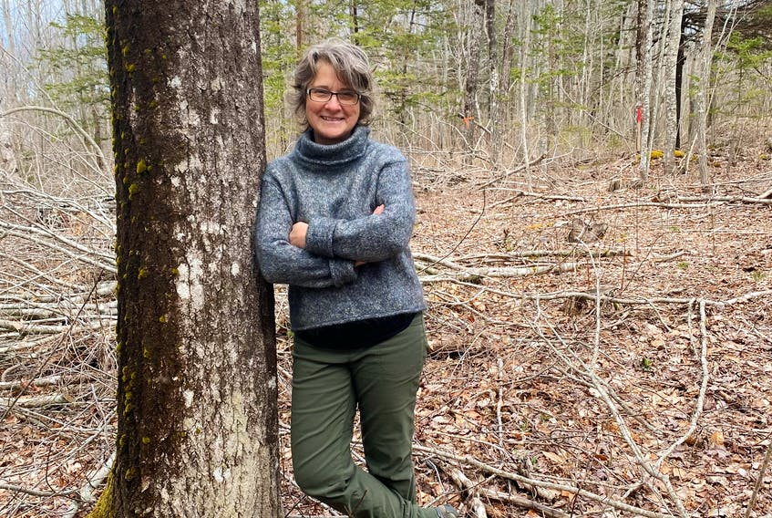 Kris Humphreys of the Arlington Forest Protection Society is shown on a 46.7-acre section of forest purchased in January to protect it from clear-cutting. - Contributed