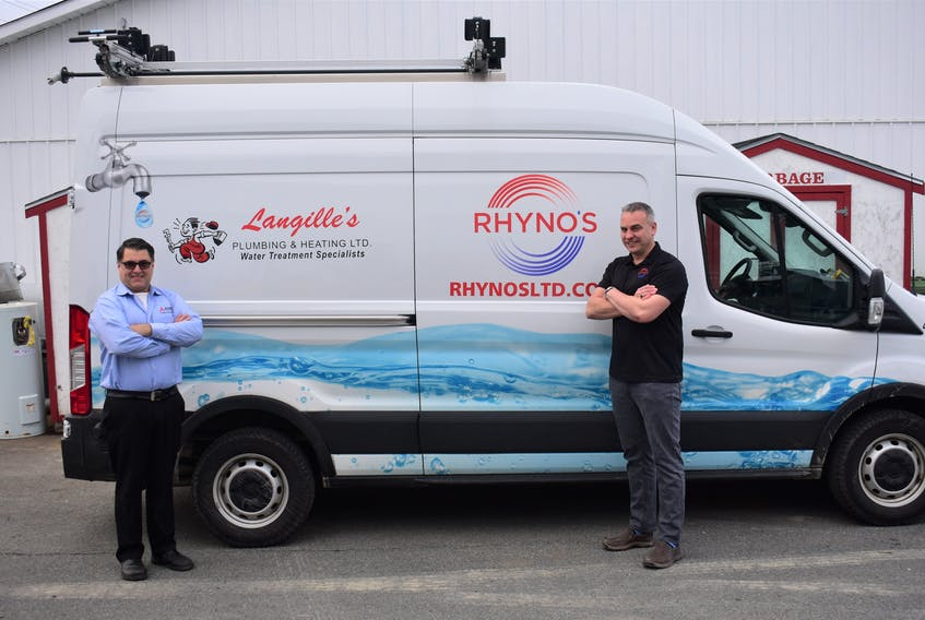 Jayme Rhyno (right) of Rhyno's Heating, Ventilation, Air Conditioning & Refrigeration celebrates one year of merging businesses with Paul Langille (left) from Langille's Plumbing & Heating Limited. - Photo Contributed.