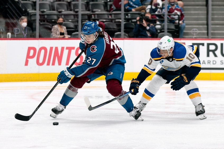 Colorado Avalanche defenceman Ryan Graves (27) controls the puck under pressure from St. Louis Blues center Brayden Schenn (10) in Game 2of the first round of the 2021 Stanley Cup Playoffs at Ball Arena in Denver. - Isaiah J. Downing