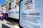 A healthcare worker at The Children's Hospital of Eastern Ontario gets a free cone from an ice cream truck outside the hospital.