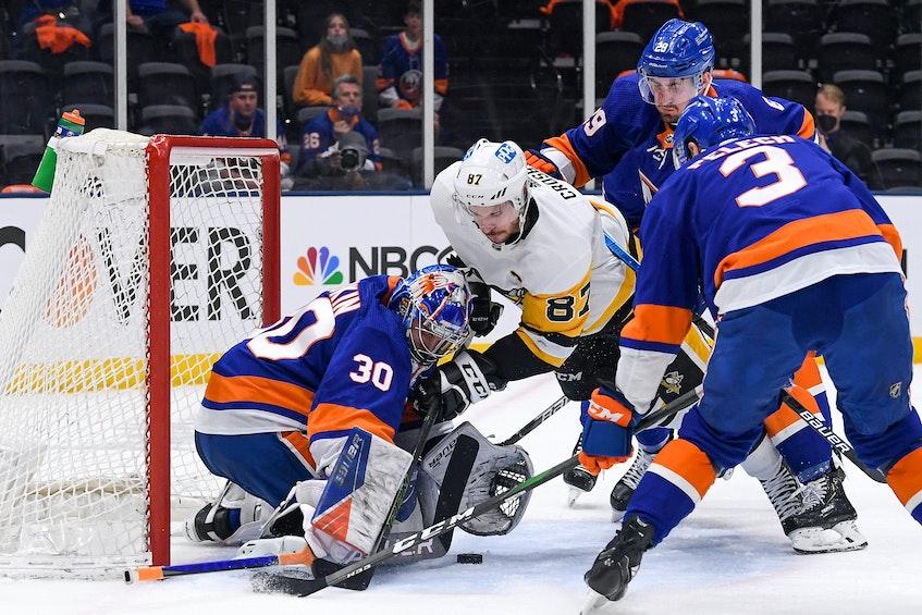 New York Islanders centre Brock Nelson (29) checks Pittsburgh Penguins centre Sidney Crosby (87) in front of goaltender Ilya Sorokin during the first period of Game 6 of the first round of the 2021 Stanley Cup Playoffs at Nassau Veterans Memorial Coliseum on Wednesday. - Dennis  Schneidler
