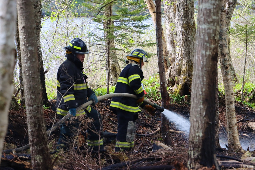 Firefighters douse a woods fire that broke out along Nature Haven Road in Lake Paul on May 25. – Adrian Johnstone - Contributed