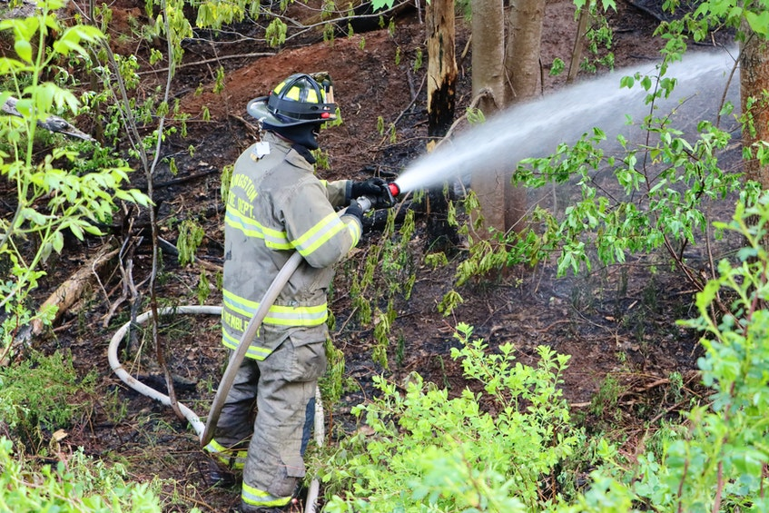 A firefighter dispatched out of Kingston responds to a small woods fire along Greenwood Road on May 25. – Adrian Johnstone - Contributed