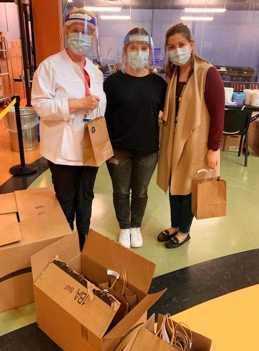 Three of the workers at the Membertou COVID-19 assessment centre with their care packages, which were dropped off at the back entrance. Each package included healthy snacks and a candle. CONTRIBUTED  - Contributed