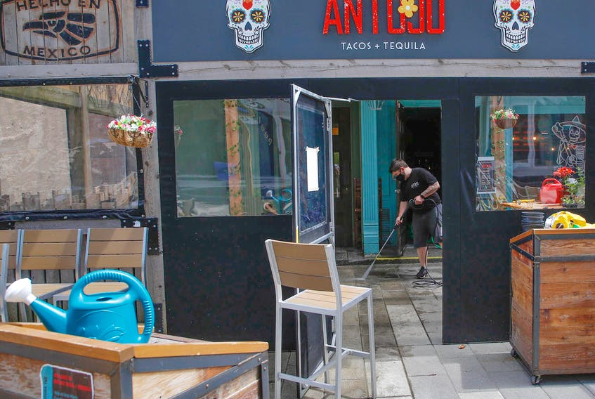 FOR NEWS STORY: Antojo manager, Jon Whitton, uses a pressure washer to begin cleaning the patio of the Argyle Street restaurant Friday May 28, 2021. Whitton, as well as many other Nova Scotians is anticipating the loosening of COVID19 restrictions later today.  TIM KROCHAK PHOTO