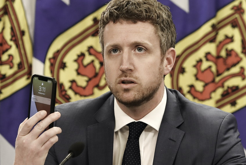 May 3, 2021 - Nova Scotia Premier Iain Rankin holds up a cellphone while asking young people to research the effects of the variants of COVID-19 during an online update on the state of the pandemic in the province on Monday, May 3, 2021.