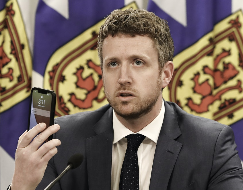 Nova Scotia Premier Iain Rankin holds up a cellphone while asking young people to research the effects of the variants of COVID-19 during an online update on the state of the pandemic in the province on Monday, May 3, 2021. - Communications Nova Scotia