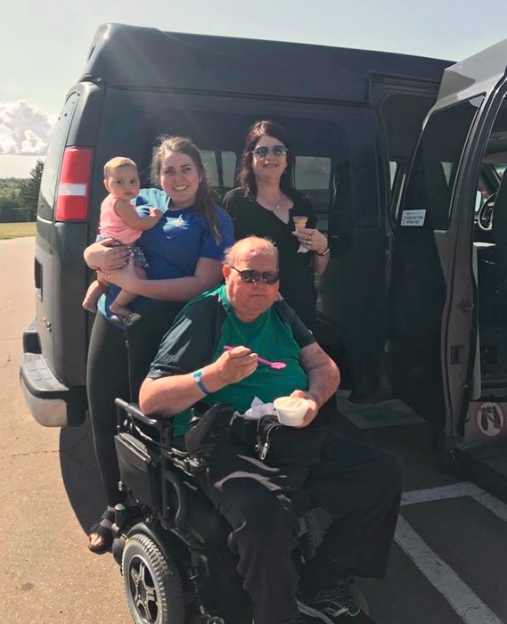 Taylor Pound, left, holding a baby cousin, stands with her mom, Betty Pound, and her father, Allan Pound, seated in his wheelchair, at Marco Polo Land in August 2017. The Pounds passed on the van when Allan died and it continues to be donated to new owners. - Contributed