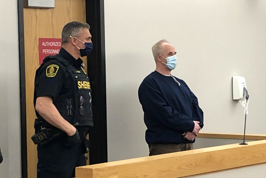 Escorted by sheriffs, Dennis Murphy (right) stands as provincial court Associate Chief Judge Mike Madden enters the courtroom for his sentencing in St. John's Monday.