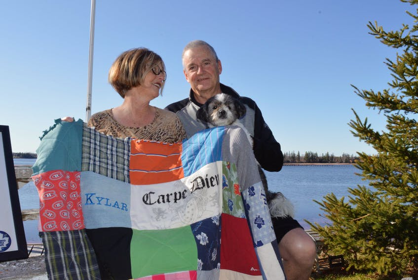 Williams and and her partner Bob Terweeme show off a quilt made from Kylar's old clothes.