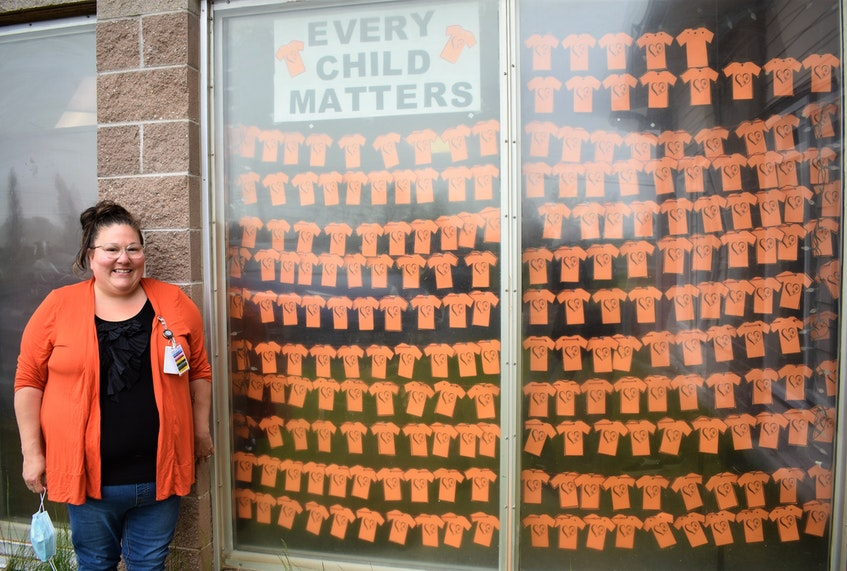 """Annie Knockwood stands by the Indian Brook Medical Centre window display of cut-out T-shirts. There are 215 in total to represent, as Knockwood said, """"one for every life."""" - Richard MacKenzie"""