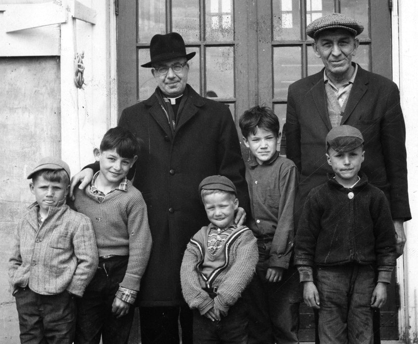 Father William Barnardo, a parish priest, and Chief Simon Nevin with group of boys on the Shubenacadie residential school steps August 5, 1965. - File