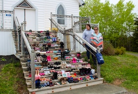 Gina Hrachy left, and Maxine Kennedy, both of Mira Road, add their contributions to the shoes left on the steps of St. Anne's Church in Membertou. IAN NATHANSON/CAPE BRETON POST