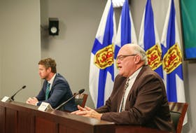 Nova Scotia Premier Iain Rankin listens as Dr. Robert Strang, the province's chief medical officer of health, speaks at a COVID-19 briefing in Halifax on Friday, May 28, 2021.