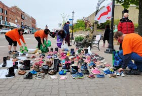 Demonstrators begin removing shoes to be taken for a ceremony at Abegweit First Nation.