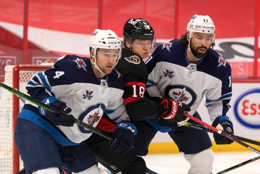 Winnipeg Jets defenceman Neal Pionk (4) and centre Nate Thompson defend against Ottawa Senators rookie Tim Stuetzle on Monday night at the Canadian Tire Centre.