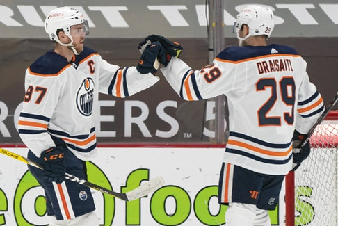 Connor McDavid (97) of the Edmonton Oilers celebrates with teammate Leon Draisaitl (29) after scoring a goal against the Vancouver Canucks at Rogers Arena on May 3, 2021.