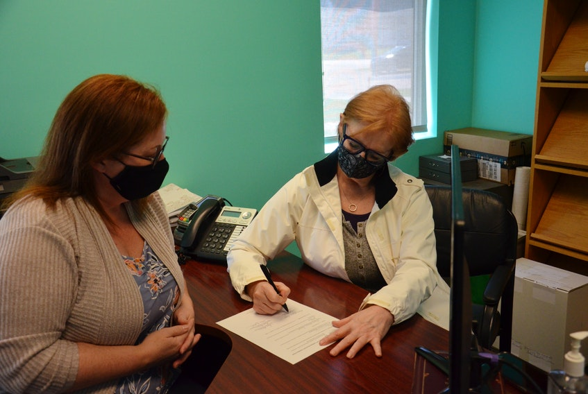 Anne Marie Shea, right, signs the withdrawal of candidate form for the Rural Municipality of Kinkora byelection held Monday as chief administrator officer Tina Harvey looks on. Shea and Amanda Dwyer tied with 43 votes. Shea decided on Tuesday to withdraw, giving the seat to Dwyer. Harrison Duffy, who received 78 votes, was also voted onto council.