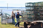 Hailey Scotland and Robert Heighton Jr. loading traps as part of work for the Ocean Rider 1 lobster boat which fishes from off the Cape John Wharf.