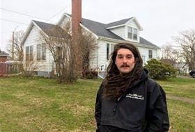 Tyler Leamont, 31, stands in front of the four-bedroom residence on Spring Park Road he moved into last October. The neighbourhood was rezoned in 2019 and the house is set to be demolished this June. Leamont and his two roommates were given three months to vacate it.