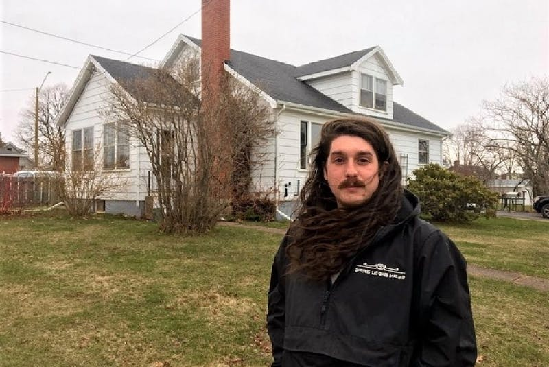 Tyler Leamont stands in front of the four-bedroom residence on Spring Park Road he moved into last October. - Rafe Wright/Special to The Guardian
