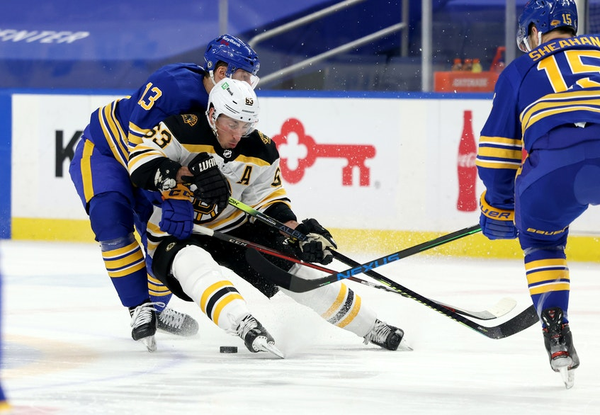 Buffalo Sabres centre Tobias Rieder (13) knocks Boston Bruins winger Brad Marchand (63) off the puck during an April 22 game at Buffalo's KeyBank Center. - Timothy T. Ludwig-USA TODAY Sports