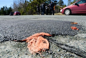 A pothole, filled with sand bags with a layer of asphalt over them, served as a backdrop to a Progressive Conservative media availability on Bennett's Road in St. Philip's Tuesday morning. Interim PC leader David Brazil said the government has to have a better prioritizing system for road repairs and upgrades. Keith Gosse/The Telegram