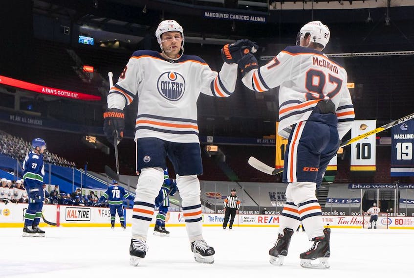 Connor McDavid (97) of the Edmonton Oilers is congratulated by teammate Leon Draisaitl (29) after scoring a goal against the Vancouver Canucks at Rogers Arena on May 3, 2021, in Vancouver.