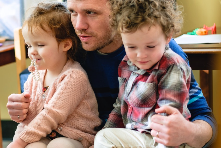 Twins Iris MacKenzie, left and Duncan MacKenzie, sit with their father Kenneth MacKenzie during a Gaelic play time event in Mabou. The twins will be among the students expected to eventually attend Taigh Sgoile na Drochaide when it opens in Mabou in the fall. CONTRIBUTED