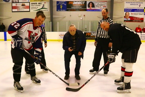 Robin Lowthers, left, and Bradley Burgess were at the ready as Wayne Lunn, brother of the late Gary Lunn, prepared for the ceremonial puck drop at a special exhibition game in April.  JIM IVEY