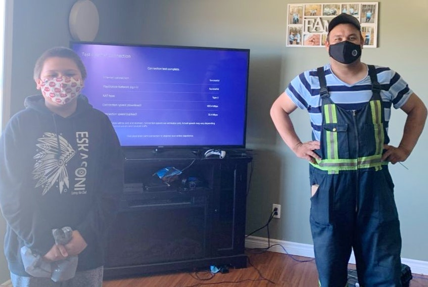 Twelve-year-old Allan Sylliboy is all smiles under his mask as Arin Stevens, a technician with Eskasoni Communications, installs high-speed Internet to the home. CONTRIBUTED