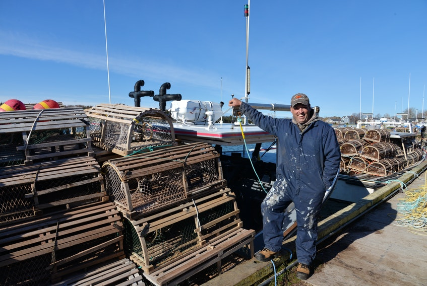 Blake Buote stands next to his boat - The Bella Marie - before leaving the North Rustico Harbour for the open water on Tuesday for the start of spring lobster season to set lobster traps.